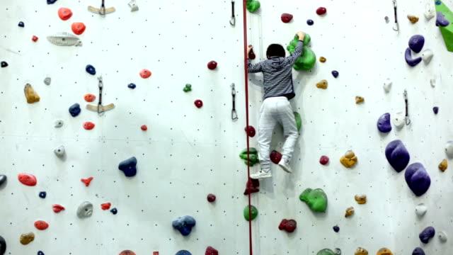 Video Sweet little preschool boy, climbing wall indoors