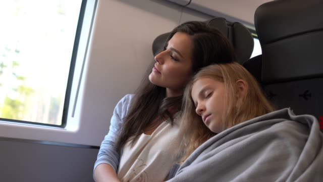 sweet loving mother covering her daughter asleep and leaning against her shoulder on train - nazionalità russa video stock e b–roll