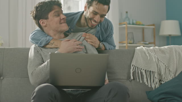 Sweet Male Queer Couple Spend Time at Home. Young Man Uses a Laptop, His Partner Comes From Behind and Gently Embraces Him. They Laugh and Touch Hands. Room Has Modern Interior. Sweet Male Queer Couple Spend Time at Home. Young Man Uses a Laptop, His Partner Comes From Behind and Gently Embraces Him. They Laugh and Touch Hands. Room Has Modern Interior. Shot on RED EPIC-W 8K Helium Cinema Camera. gay man stock videos & royalty-free footage