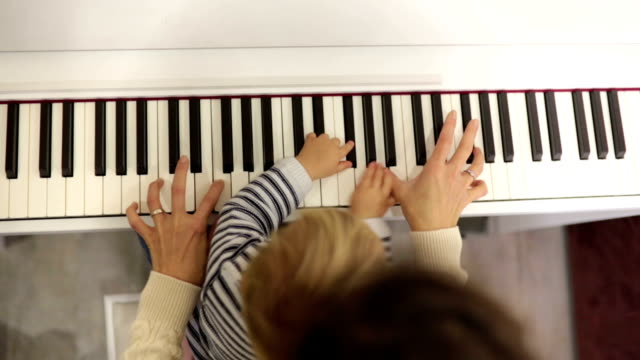 Sweet positive toddler child and mom playing piano. Early music education for little kids.