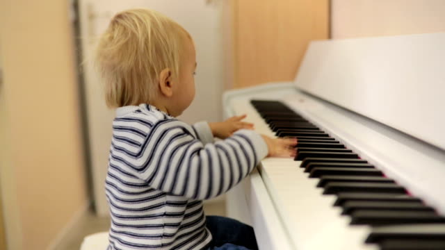Sweet positive toddler child playing piano. Early music education for little kids.