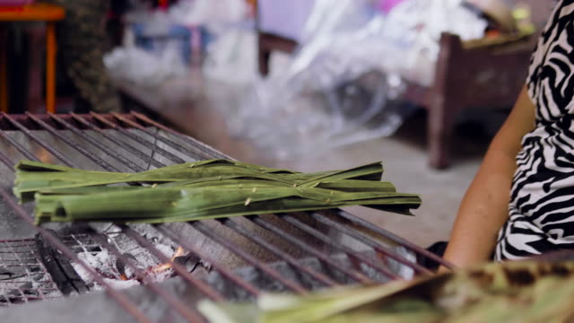 Sweet sticky rice with banana pastry covered by banana leaf grilled on barbecue.