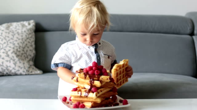 Sweet toddler birthday boy, eating belgian waffle with raspberries and chocolate at home