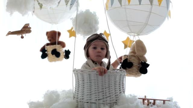 stockvideo's en b-roll-footage met zoete peuterjongen, die met vliegtuig en teddybeer speelt, luchtballons met speelgoed achter hem - sleeping illustration