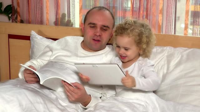 sweet toddler daughter girl with tablet computer and bald head dad man read book video