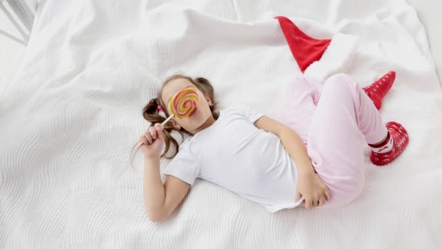 Sweet video of gorgeous kid with funny pigtails waking up and licking red-yellow candy on stick, enjoying the moment.