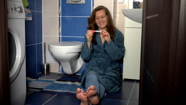 Sweet woman sitting on bathroom floor showing positive pregnancy test to camera video