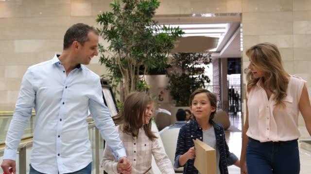 vídeos de stock, filmes e b-roll de família nova doce nas mãos da terra arrendada do mall ao andar e ao falar muito felizes - shopping center