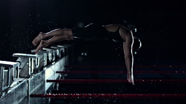 swimmer jumping off the starting block - tuffarsi video stock e b–roll
