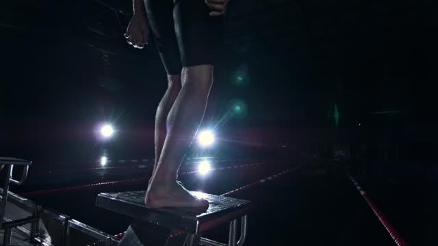 vidéos et rushes de swimmer jumping off the starting block - starting block