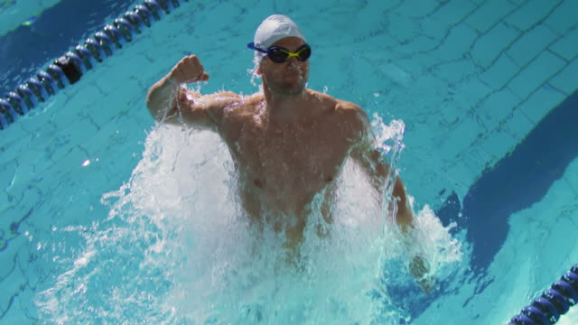 Swimmer training in a swimming pool Front view of a young Caucasian male swimmer training in a swimming pool, emerging from water, smiling and punching the air athleticism stock videos & royalty-free footage