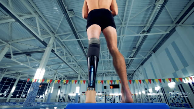 A swimmer with a leg prosthesis, bottom view.