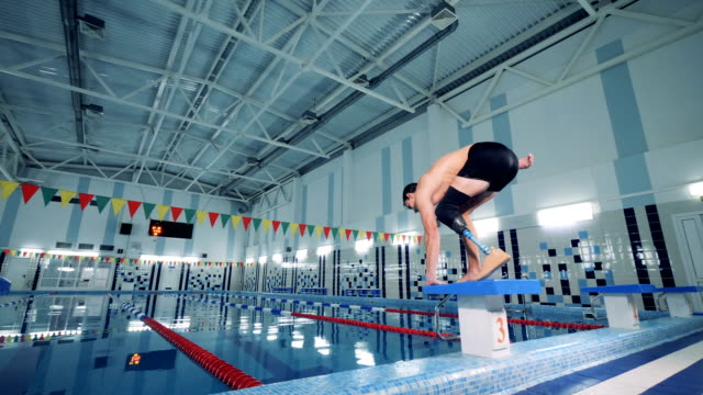 Swimmer with a leg prosthesis jumps into the pool, close up. A person with prosthetic leg jumps into a pool. amputee stock videos & royalty-free footage