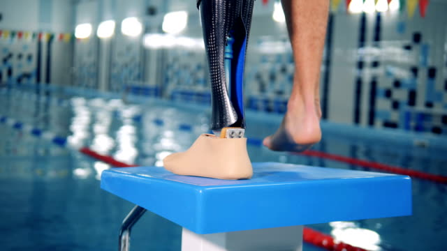 Swimmer with modern prosthesis, close up. One man wears prosthetic leg. prosthetic equipment stock videos & royalty-free footage