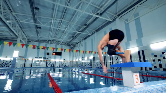 Swimmer with prosthetic leg jumping into a pool, back view. Man jumps into a pool, wearing prosthesis. prosthetic equipment stock videos & royalty-free footage