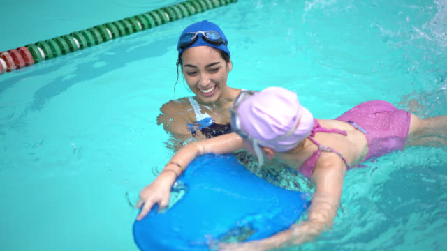 Swimming instructor teaching a little girl how to swim Female swimming instructor teaching a little girl how to swim using a swimming board and congratulating her for doing a good job swimming stock videos & royalty-free footage