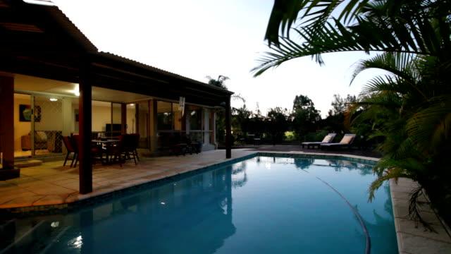 vídeos de stock e filmes b-roll de swimming pool at dusk - mansão imponente