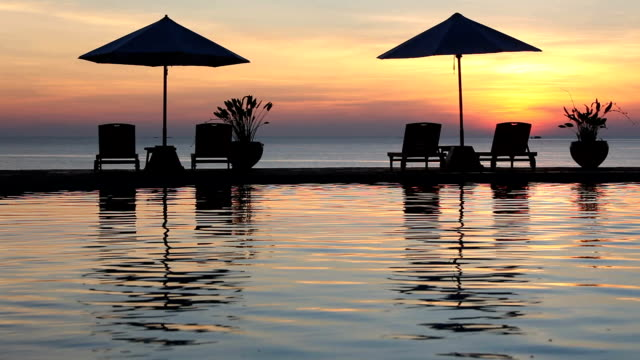 piscina sunset a myamar spiaggia, con lettini da sole - località turistica video stock e b–roll