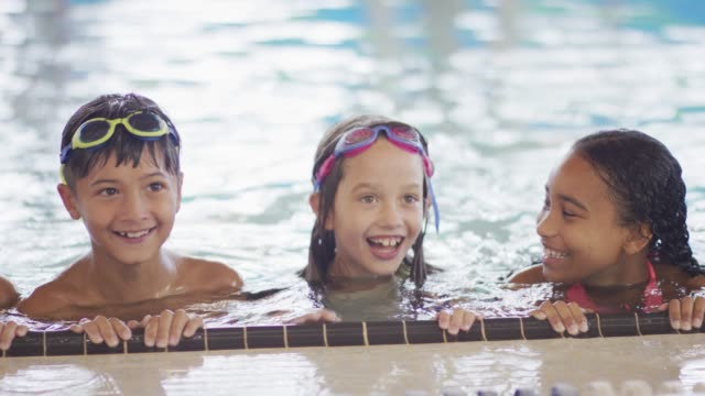 Swimming Practice A multi-ethnic group of kids are taking a swimming class at an indoor pool. They are resting at the side of the pool, while smiling at the camera. swimming stock videos & royalty-free footage