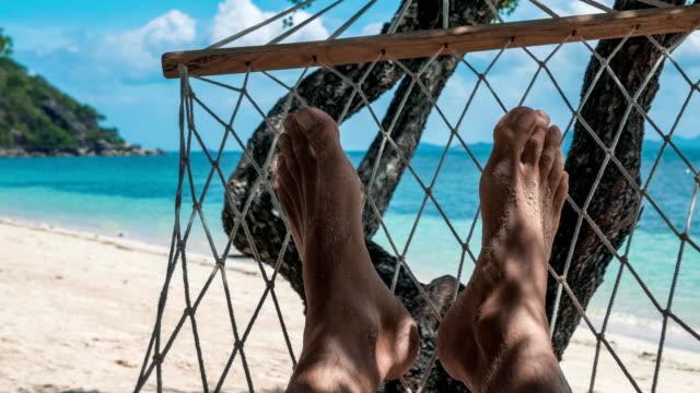swinging nackten mann füße in einer hängematte im urlaub vor dem weißen sandstrand und blaues meer - sun chair stock-videos und b-roll-filmmaterial