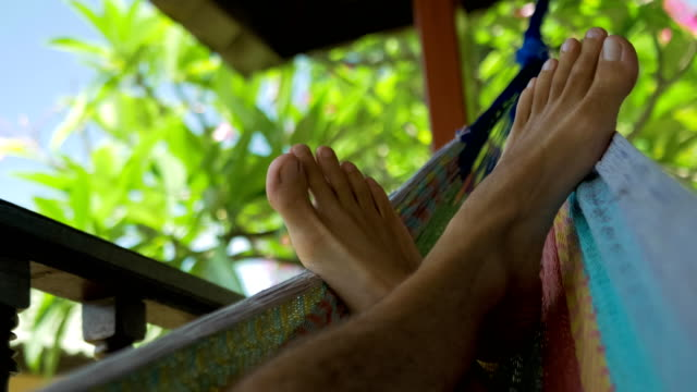 vídeos de stock e filmes b-roll de swinging bare man feets in a hammock on terrace. vacation on koh tao tanote bay, thailand - descalço