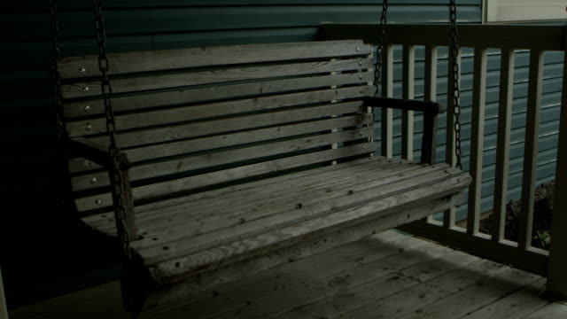 Swinging Bench A bench swings on a porch. porch stock videos & royalty-free footage