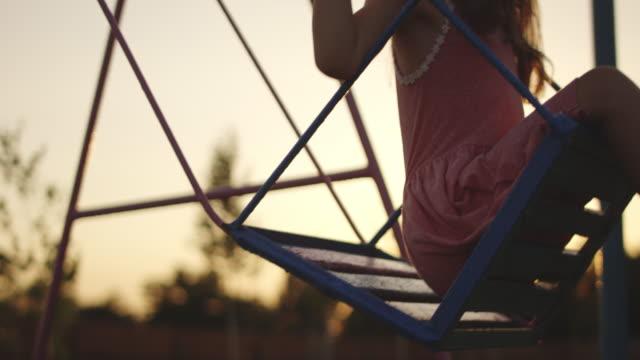 swinging girl in playground - oscillare video stock e b–roll