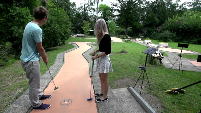 stockvideo's en b-roll-footage met swinging golf club on mini golf with young couple - mini amusementpark
