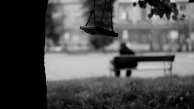 Swinging swing, man sitting on a bench in the background video