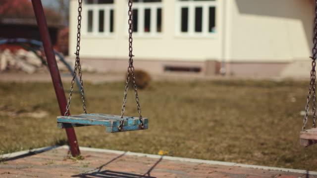 Swinging swings on empty school or park playground. stock video