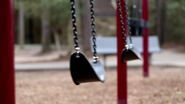 Swinging swings on empty school or park playground. video
