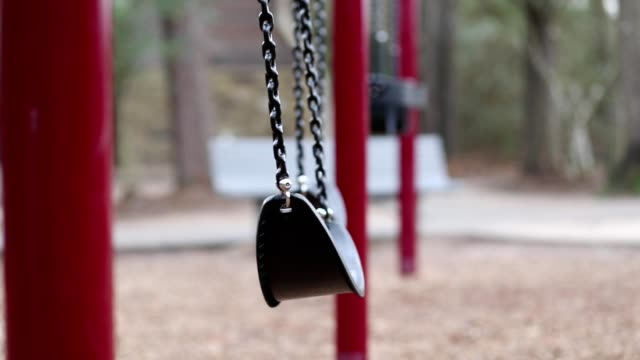Swinging swings on empty school or park playground.