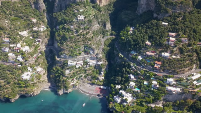 Swiss city rises up steep mountainside at edge of lake with boats video