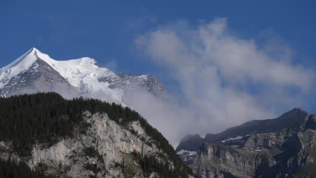 schweiziska bergslandskap med moln som passerar förbi mot en blå bakgrund - wengen bildbanksvideor och videomaterial från bakom kulisserna