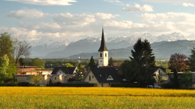 vídeos y material grabado en eventos de stock de montañas suizas detrás de un prado con flores amarillas - austria