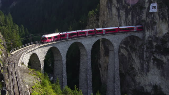 swiss red train on landwasser viaduct tunnel on bernina pass glacier express in switzerland - поезд стоковые видео и кадры b-roll