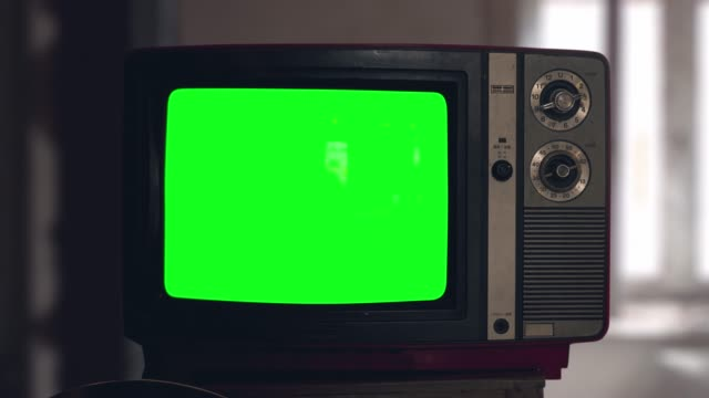 Switch on tuning an old tube vintage TV set than switch off. Wooden style retro Tv set with switchers. Old Fashioned TV Turns On. Green screen chromakey. Reflections on screen