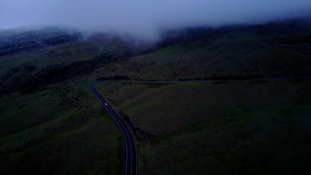 stockvideo's en b-roll-footage met switchback weg aan kant van maui vulkaan door drone - mist donker auto
