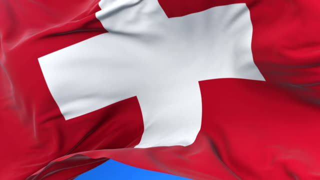 Switzerland flag waving at wind in slow in blue sky, loop video