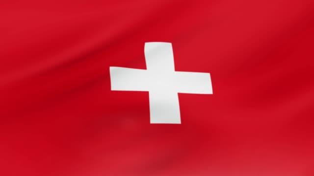flaga szwajcarii macha w filmie wideo wiatr realistyczna szwajcaria tło flagi. szwajcaria flaga zapętlanie zbliżenie - szwajcaria filmów i materiałów b-roll