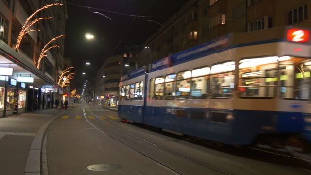 switzerland night illumination zurich famous theatersrasse traffic street panorama 4k - tranvia video stock e b–roll