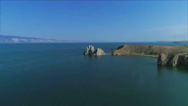 vídeos de stock e filmes b-roll de symbol of lake baikal cape burhan in summer time. drone footage - lago baikal