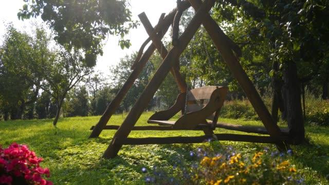symbolisk tom swing bland blommorna i trädgården - sentimentalitet bildbanksvideor och videomaterial från bakom kulisserna