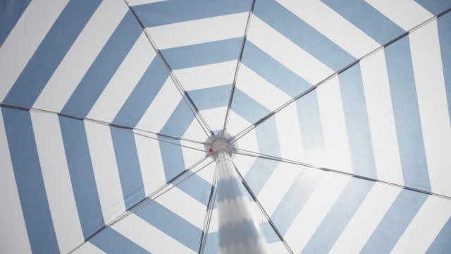 vídeos de stock e filmes b-roll de symbols of summer: spinning beach umbrella - guarda chuva