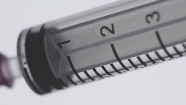 beyaz bir arka plan üzerinde enjeksiyon ilaç dolum bir şırınga. makro - doping stok videoları ve detay görüntü çekimi