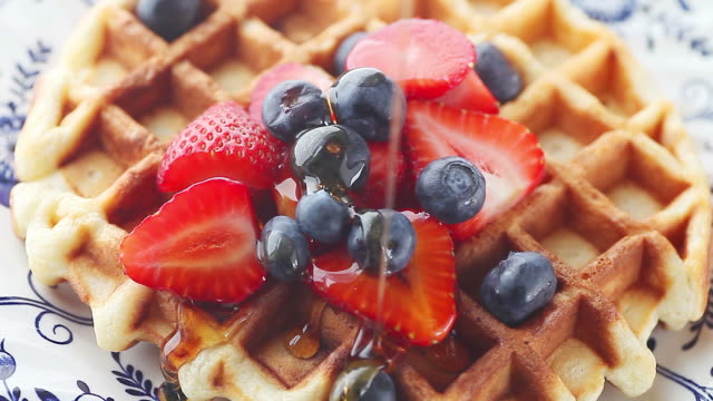 syrup on waffle with blueberries and strawberries - sciroppo video stock e b–roll