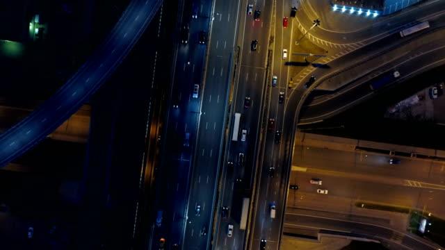 vídeos de stock, filmes e b-roll de sistema de cruzamentos de estrada em uma estrada de noite. ver os de cima. - acima