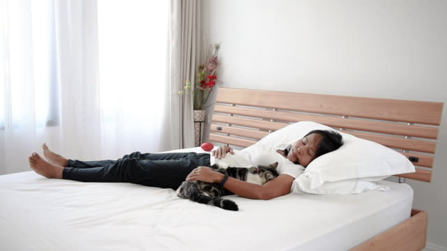 Tabby cat sleep with woman in cozy white bedroom interior