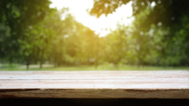 Table and Chair, Wood table bar and nature tree bokeh blurred background at morning time and beautiful nature sun light, Top wood table space area for products shows. 4096x2304. 4K UHD. Video Clip