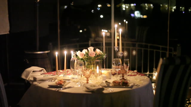 Table for a romantic dinner. Served table with candles and cutlery for lovers